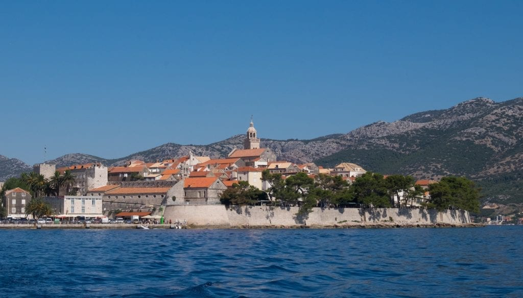 Korcula's walled old city rising up from the water, the mountains in the background.