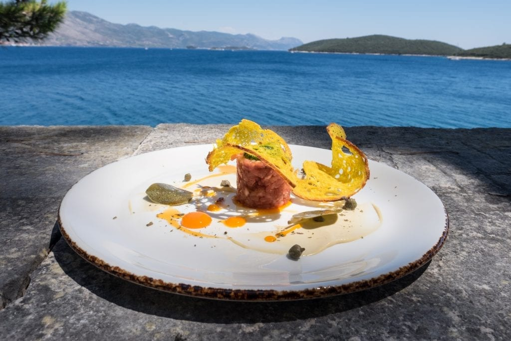 A fancy plate of food at LD restaurant on the edge of the old town overlooking the blue ocean and islands in the background. There's a Vitello tonnato looking like a beef tartare, a curved thin piece of stiff bread curved around the top, with cured caper leaves and drops of cured egg yolk on the plate.