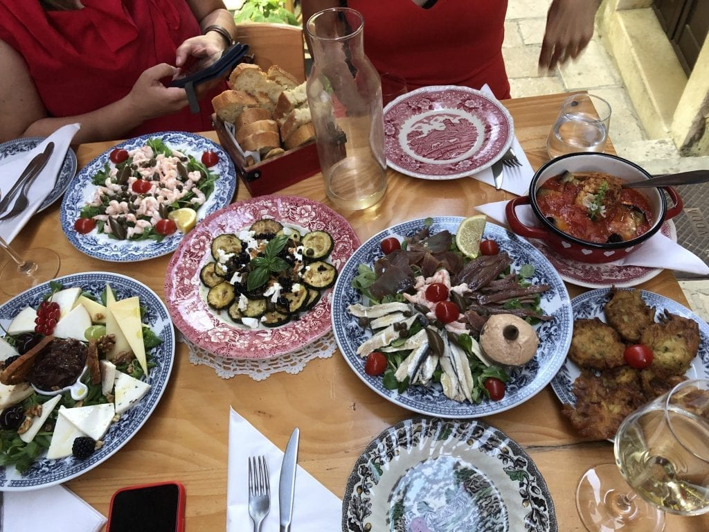 Several plates of Croatian tapas -- one with cheeses and nuts, one with zucchini slices, one with anchovies and fish pate, one with shrimp and olives, one with zucchini fritters, one with stewed eggplant in tomatoes.