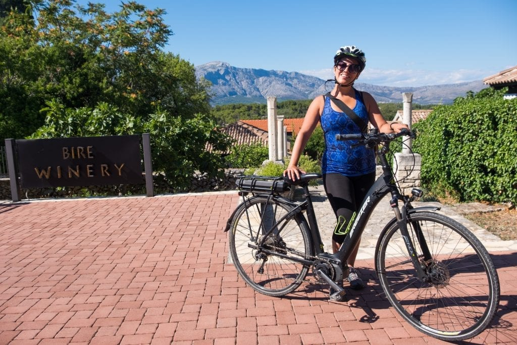 Kate stands in front of a bike, holding it and smiling, a sign for Bire Winery at the side, and mountains in the background.