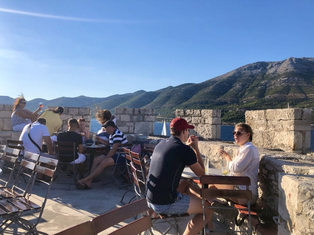 A few people sitting inside the tower at Massimo Bar, enjoying cocktails while overlooking the ocean and mountains.