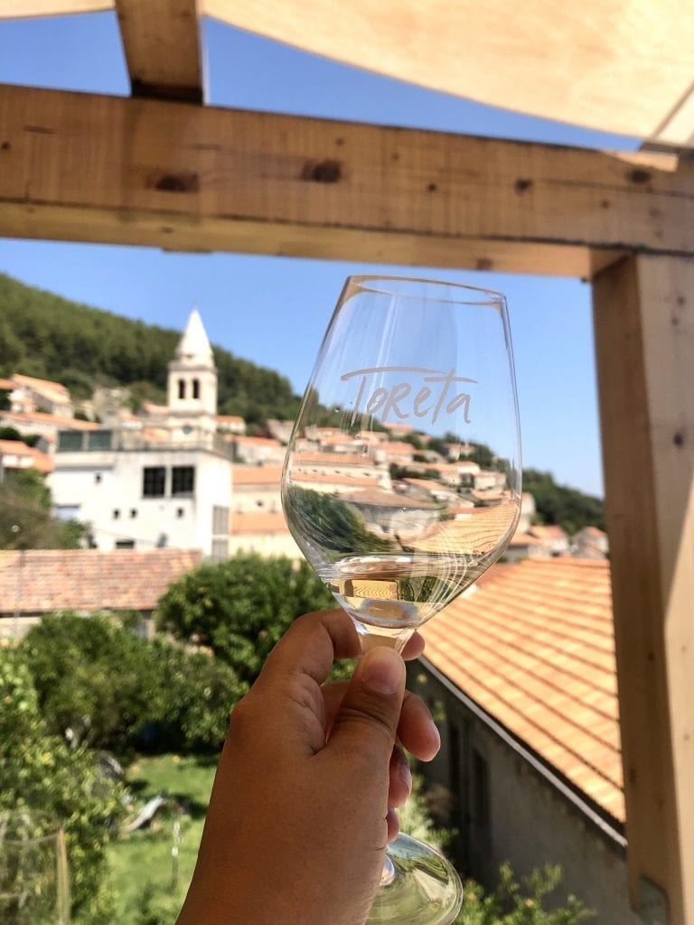 """A glass of wine reading """"Toreta"""" in the foreground; in the background, the small town of Smokvica with its church tower."""