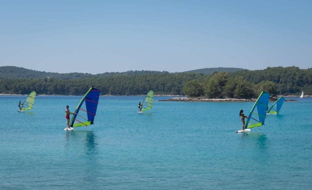 Several windsurfers practicing holding their sails up in the calm water near Badija Island.