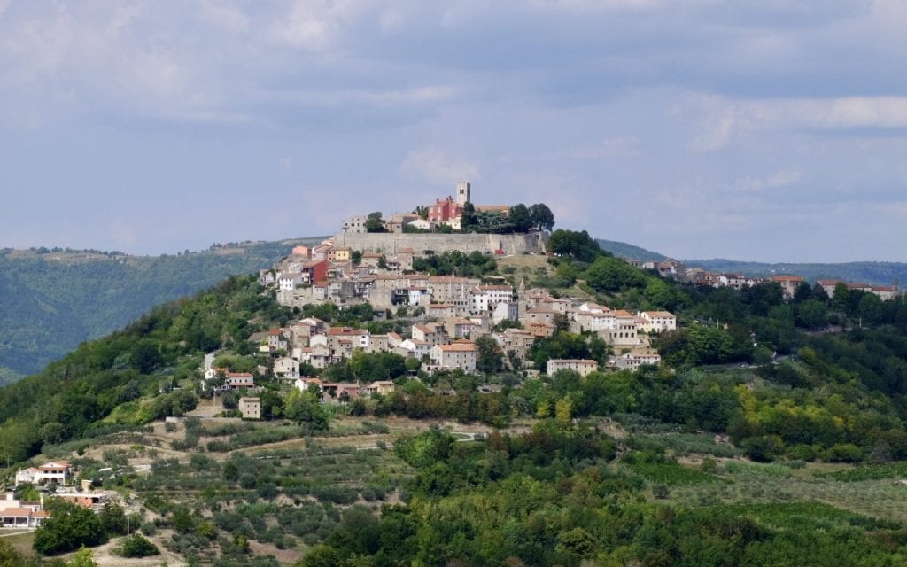 Motovun: a hill town perched on top of a bright green hill. A small wall and several rows of beige, white, and brown houses on top.