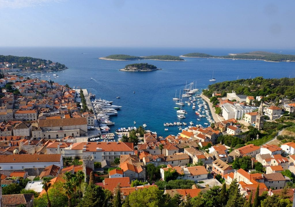 The view of Hvar from the Spanish Fortress: orange-roofed buildings and green trees surrounding a three-sided harbor edged with white boats of all sizes, the Pakleni islands in the distance, shaped like green droplets in the sea.