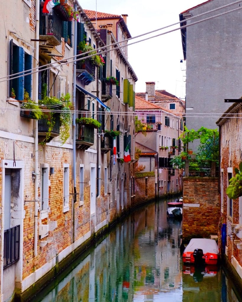 A view of Venice! A teal canal surrounded by brick walls, some with balconies with green plants dangling, some with Italian flags.