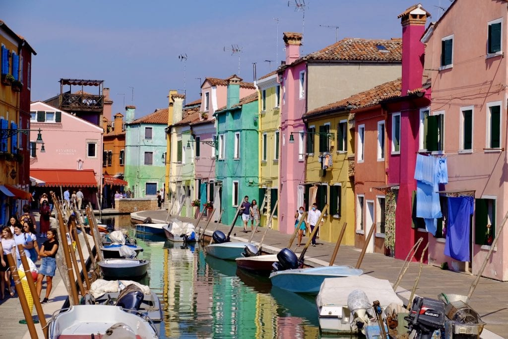The brightly colored buildings of Burano island in Venice, all set on a canal filled with small boats.