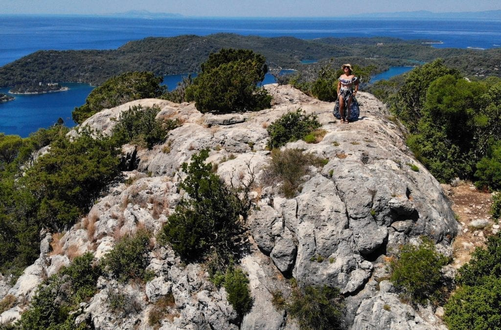 Kate standing on top of a rocky formation in Mljet, views of the island in the distance, shot from a drone above.