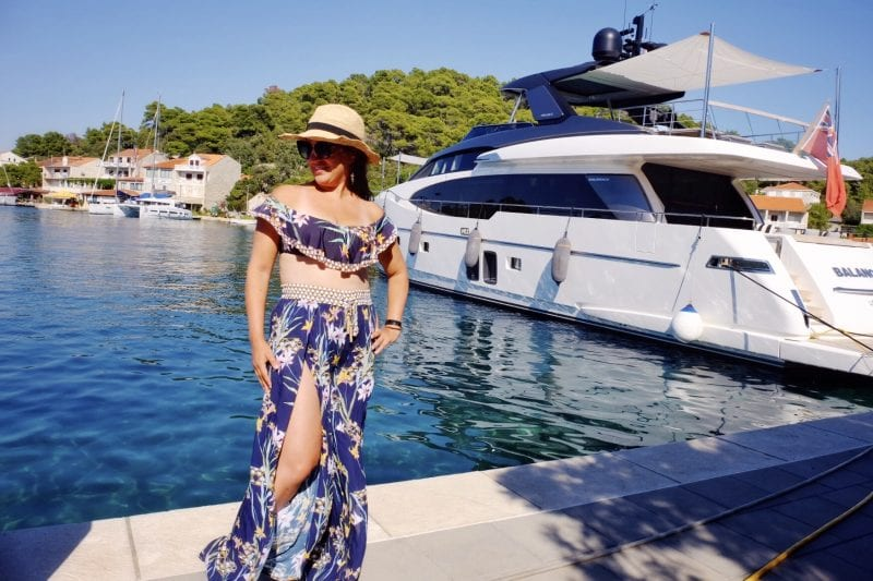 Kate stands on a pier in front of a yacht and blue water in Mljet, Croatia. She wears a straw hat and an off-the-shoulder navy blue tropical-print bikini that has matching loose pants with slits up each leg.
