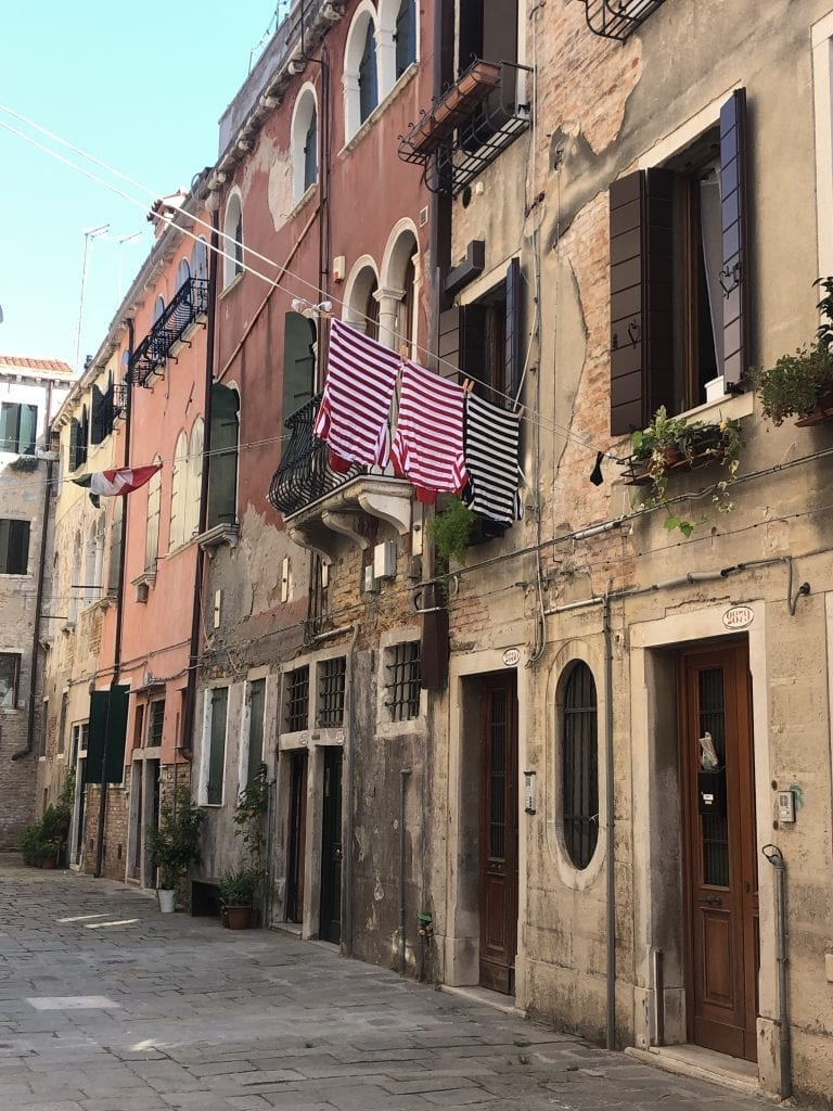 A street in Venice lined with homes. Out one window hangs laundry: two red and white striped shirts and a black and white striped shirt. The uniform of a gondolier.