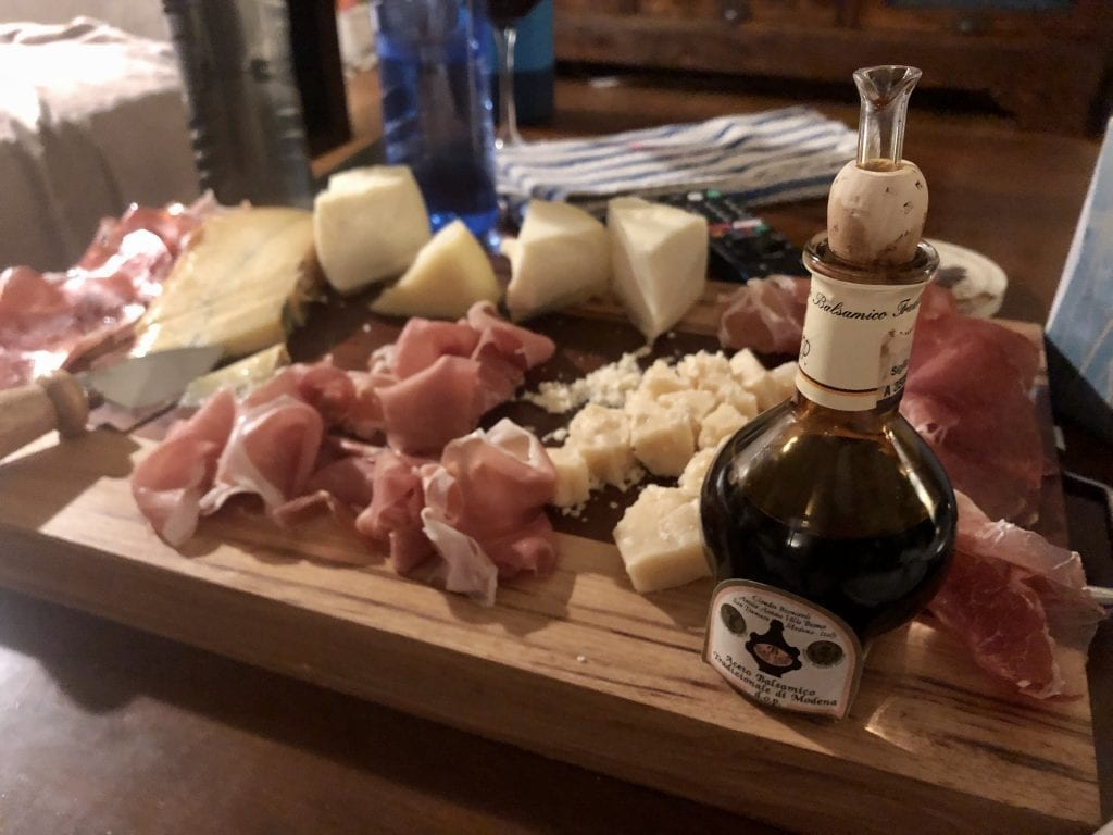 A wooden cutting board topped with various cured meats, cheeses, and a bottle of traditional balsamic vinegar from Modena.