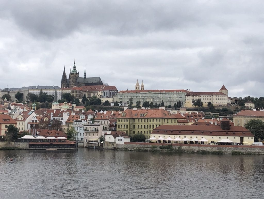 A view of Prague Castle from the Charles Bridge on a cloudy day, the spires sticking straight up from the cathedral, set on a dark gray river.