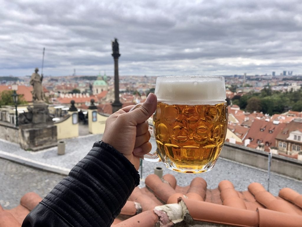 Kate's hand holds a golden beer with a nice white foam in front of the cityscape of Prague -- a view of lots of orange roofs and statues underneath a cloudy sky.