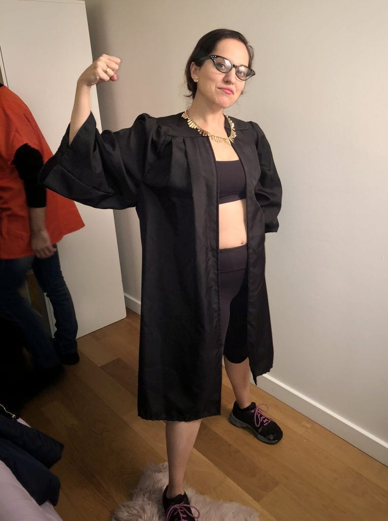 Kate's 2018 Halloween costume: Ruth Bader Ginsberg at the gym! Kate wears black glasses, an open black robe, a bright gold collar-like necklace, a black sports bra, black yoga pants, and black sneakers. She holds her arm up to show off her muscle.