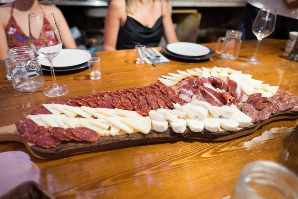 A long wooden tray covered with cured meats and sliced cheeses.
