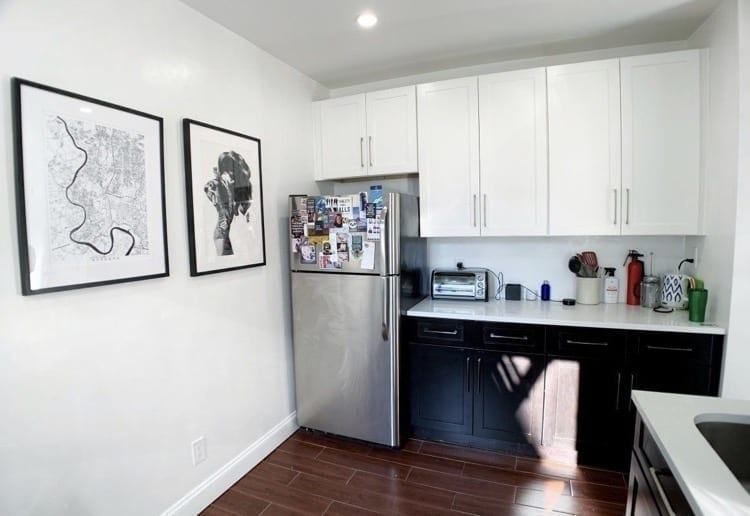 Kate's kitchen: white cabinets on top, black cabinets on the bottom, silver fridge topped with magnets, and black and white prints on the walls.