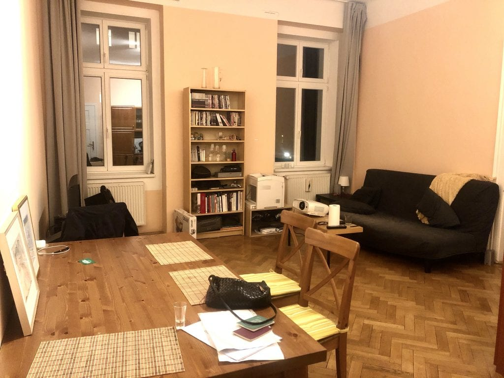 The living room: a big wooden dining table in the foreground, a bookcase with wine glasses, books, and random items in the background, with a gray futon and plastic-wood IKEA table with a projector on it.
