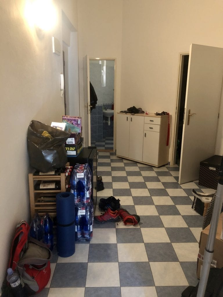 The entryway from another angle: a shoe cabinet in the back, and endless piles of clutter.