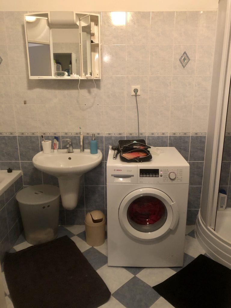The other bathroom: a sink, very high vanity, and washing machine.