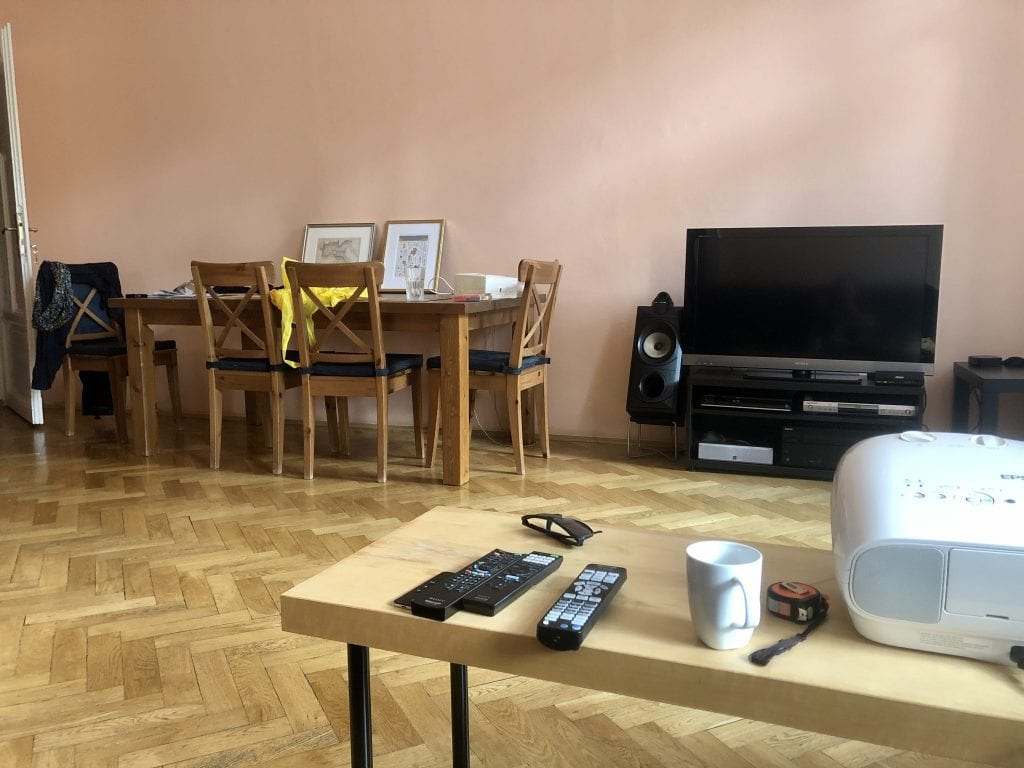 View across a living room: in the foreground, a cheap wood-and-plastic IKEA table; in the background, a large wooden dining table and a TV on a black TV cabinet.