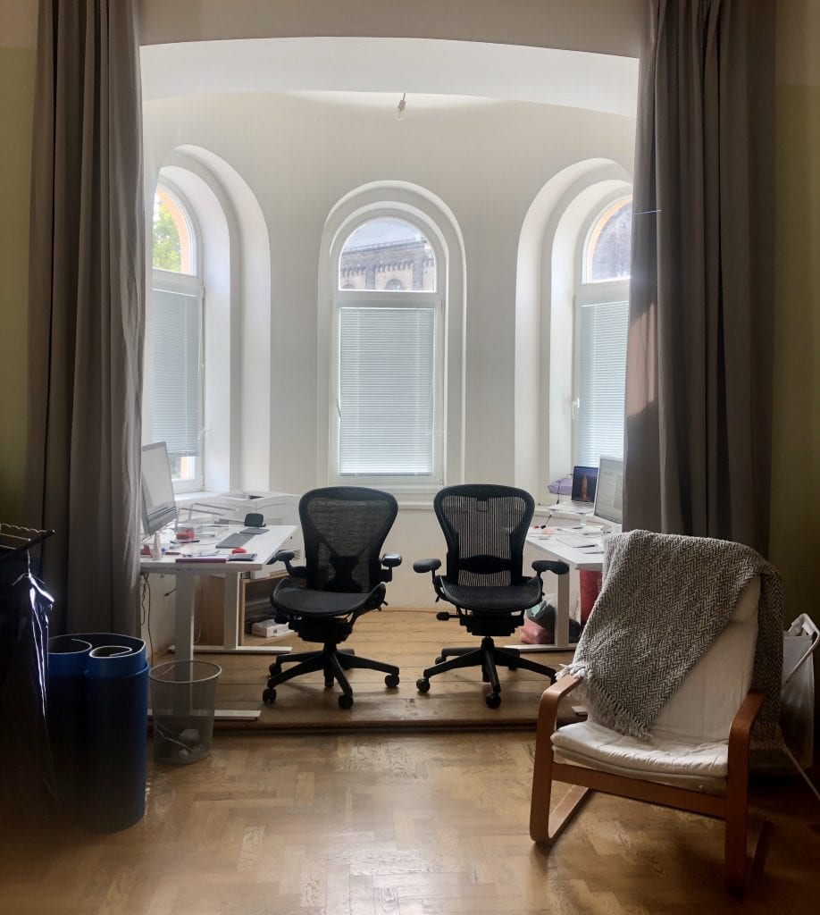 A small white room with three windows curved on top. It's a round room -- a turret! Each side has a white desk with monitors and computers on it, as well as a black office chair. Long gray curtains on each side.