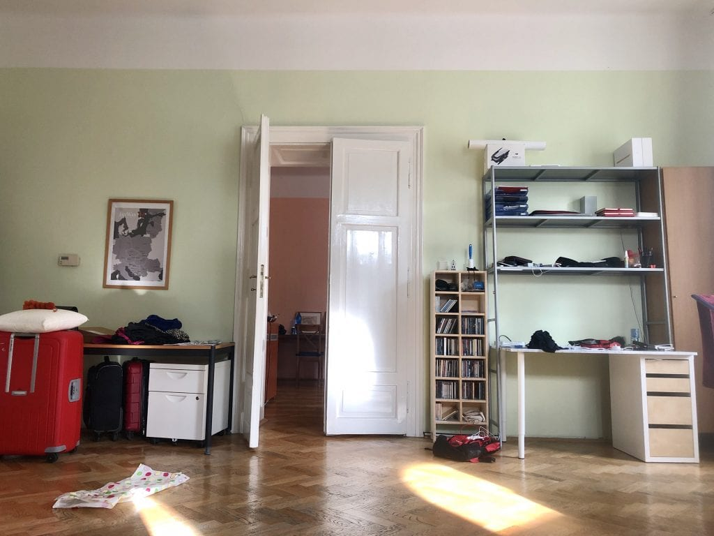 The glossy white doors from the indoor angle. On the left, a desk and lots of suitcases. On the right, a desk with lots of shelving, and a CD tower filled with CDs.