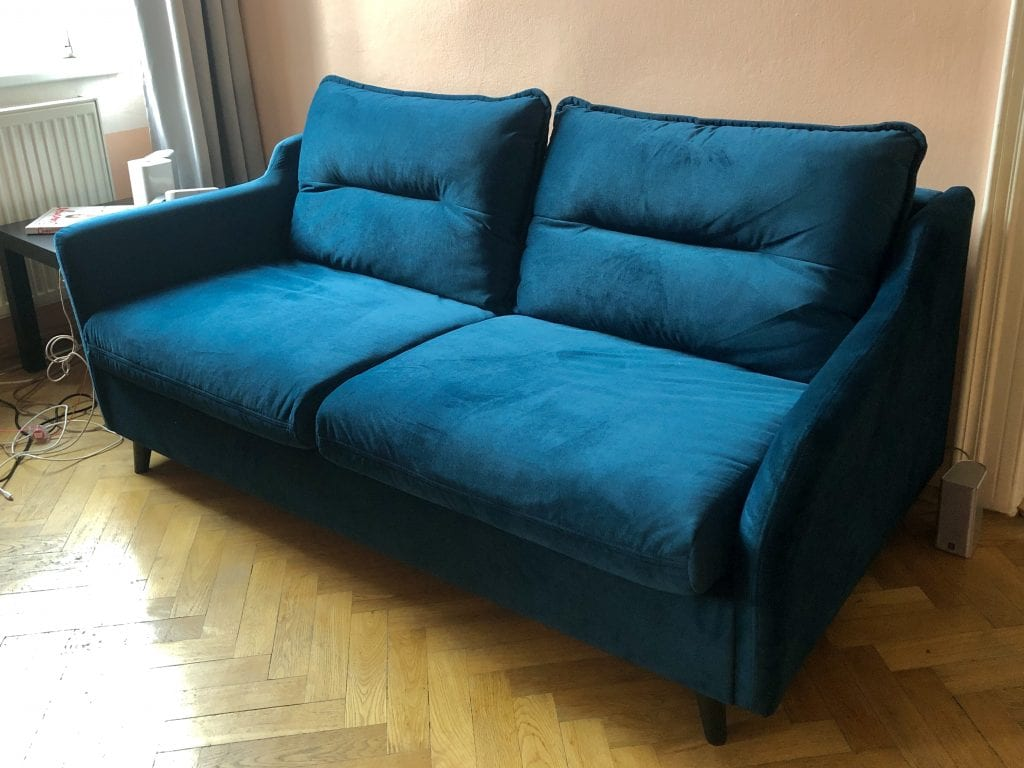 A teal microfiber couch with long rectangular cushions on top. Very modern.