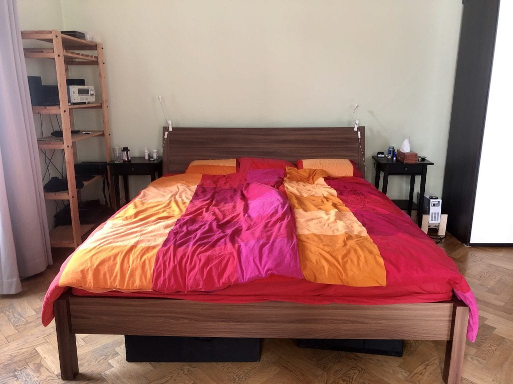A close-up view of the bed with the pink, red, and orange bedspread. Two black nightstands on each side of the table.