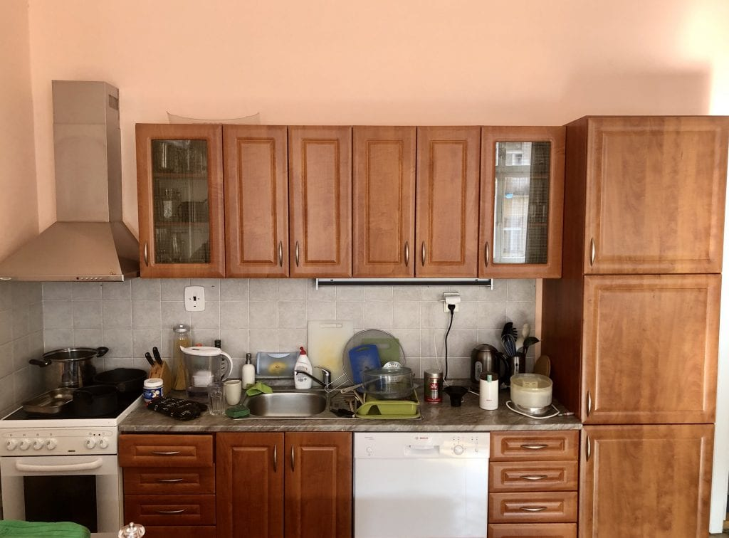 Close up on the kitchen cabinets, including a small stove, small sink, and dishwasher.