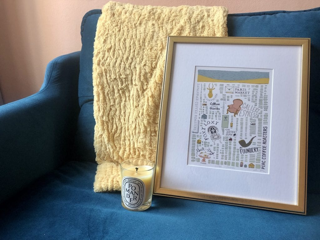 A gold-framed map of coffeeshops in Savannah, as well as a Pomander Diptique candle and a gold blanket on top of the teal couch.
