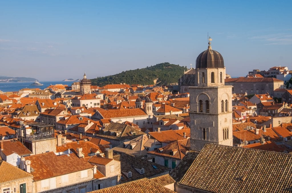 A view of the city of Dubrovnik from the walls -- lots of orange terra-cotta roofs, a church tower in the foreground, and a green island in the background, all under a blue sky.