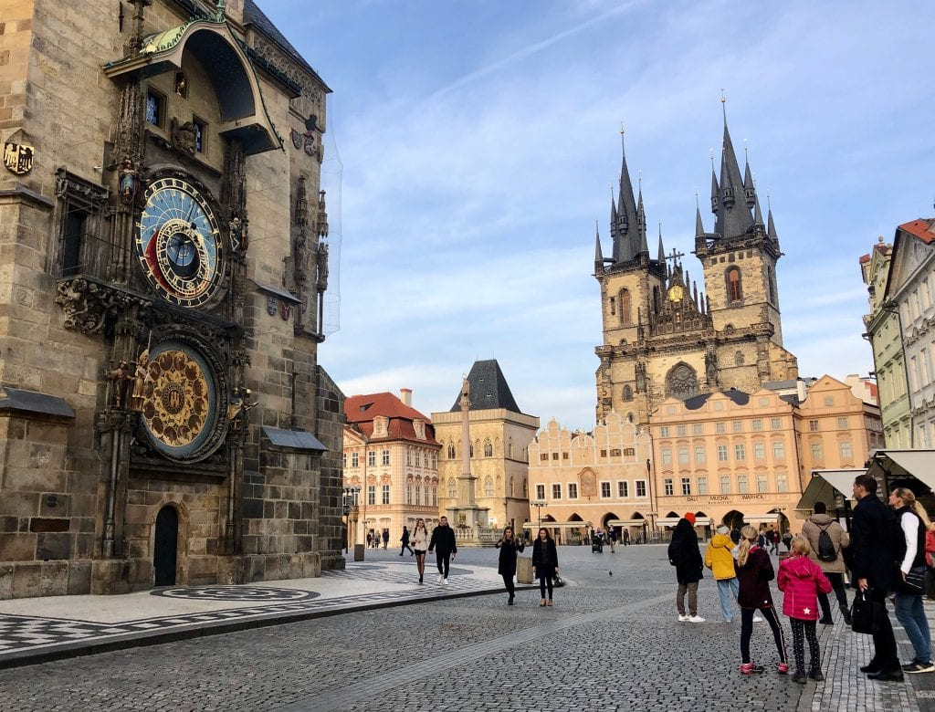A view of Prague's Astronomical Clock on the left, with a blue and gold clock and several rings moving around. In the background, Old Town Square with pointy church steeples sticking above the peach-colored buildings.