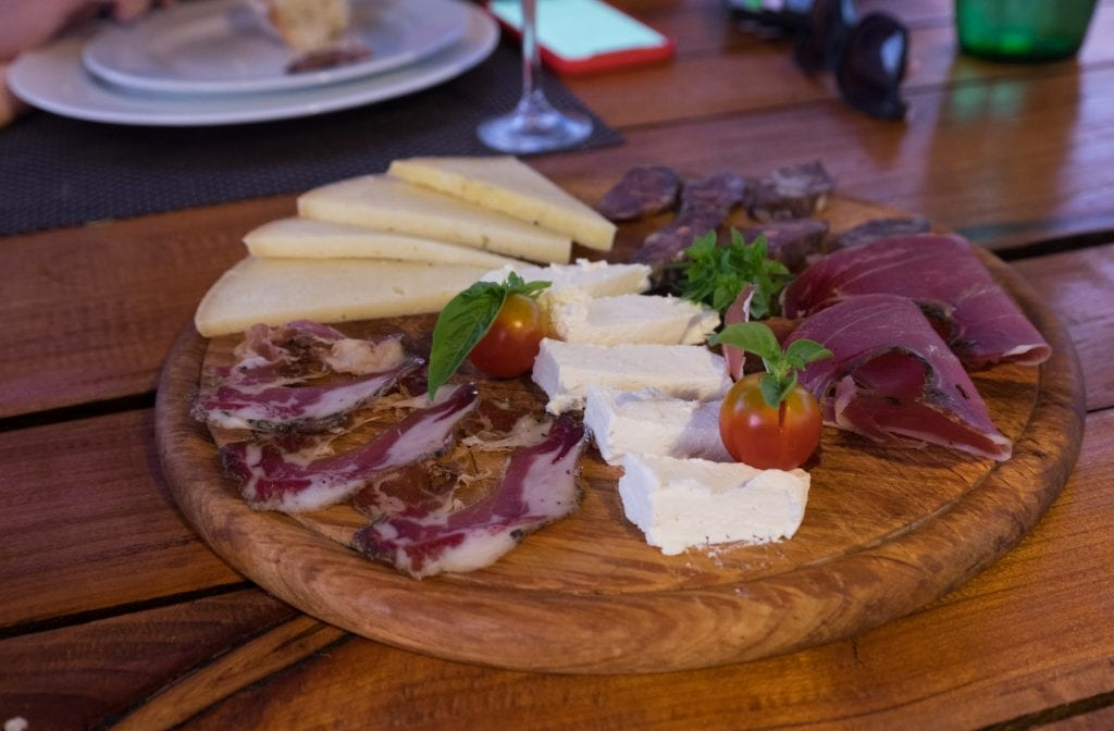 A wooden platter topped with cured meats, two kinds of cheeses, and two cherry tomatoes.