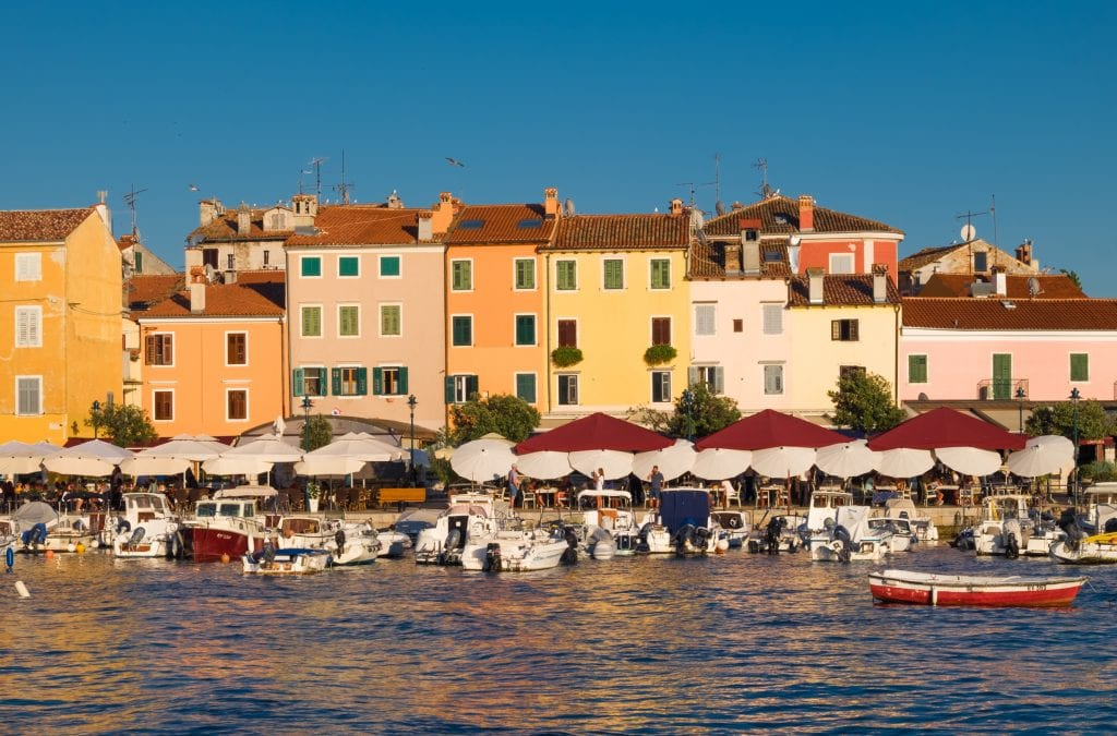 The waterfront: cafes with lots of umbrellas blocking the sun, boats in the water, and on shore, several orange, yellow, and pink homes with green shutters.