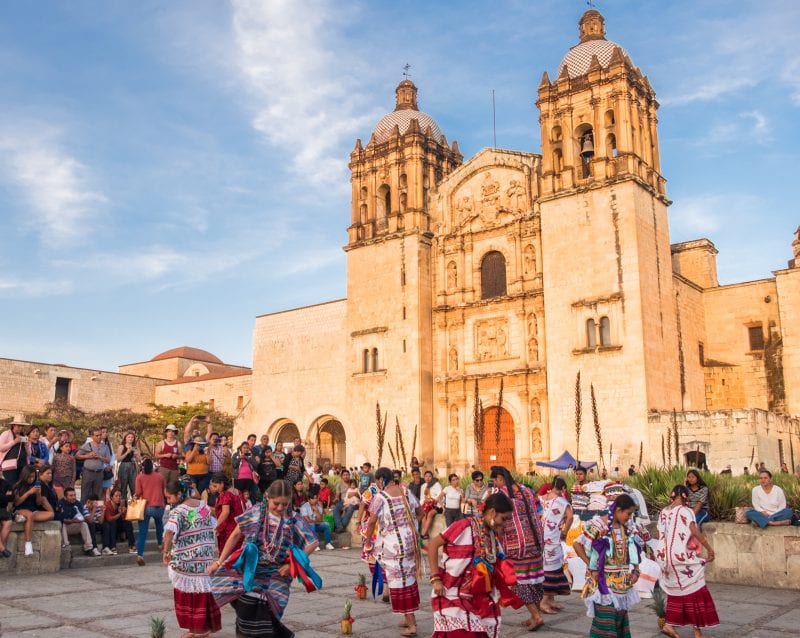 Indigenous women dancing in brightly colored dresses in front of the brightly lit cathedral underneath a blue sky in Oaxaca, Mexico.