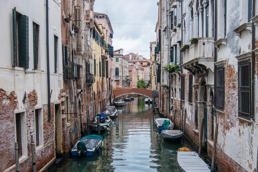A canal in Venice surrounded by brick-and-plaster homes with balconies brimming with flowers, a bridge in the distance.