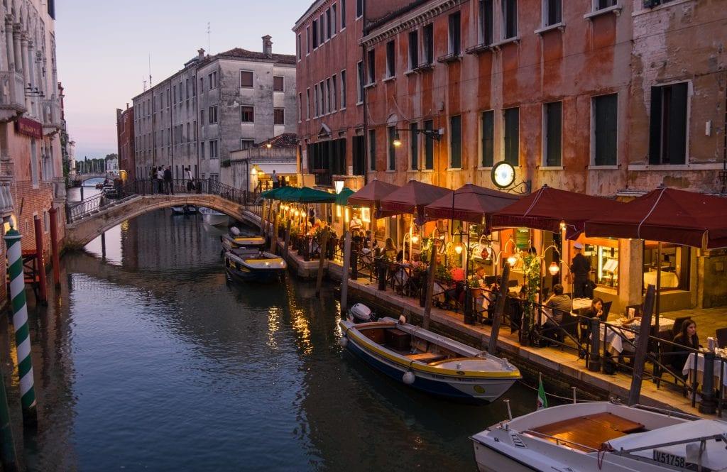 Brightly lit cafe alongside a canal in Venice.