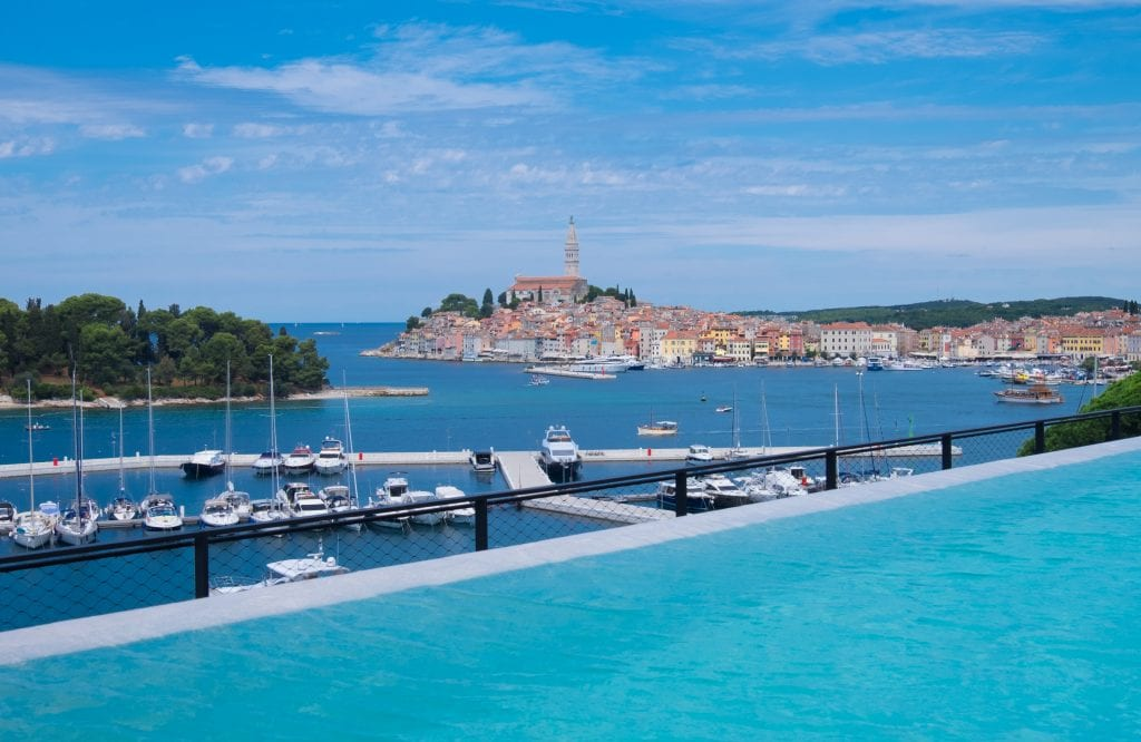 The view of the city of Rovinj with a bright blue infinity pool in the foreground.