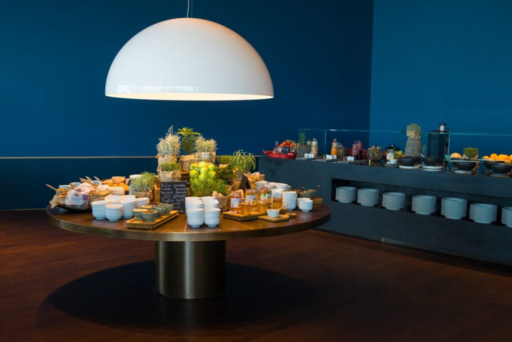 A golden buffet table in a dark blue room laid out with bowls, jams, and fruits.