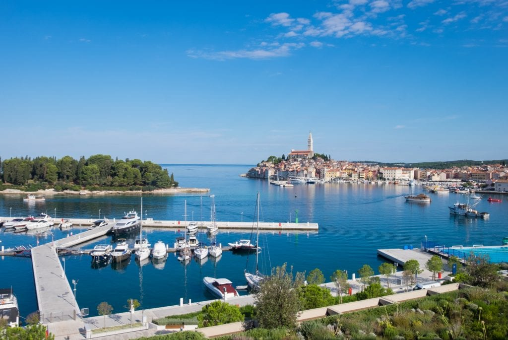 View from the hotel: the city skyline of Rovinj, and in front of it, a pier with several boats docked.