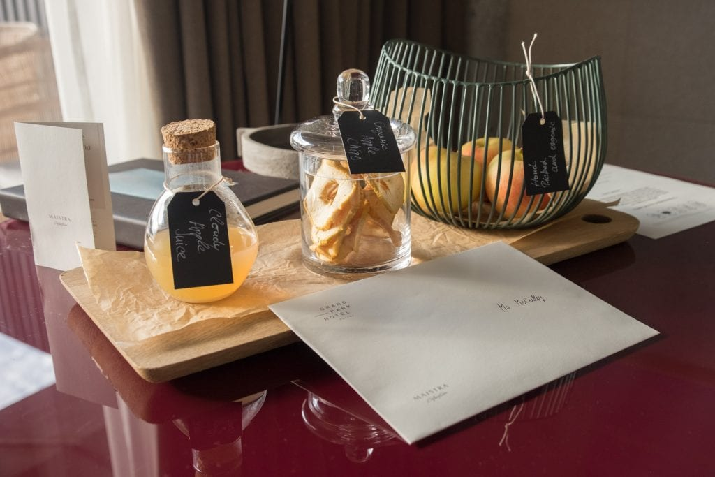 "Gifts at the hotel: an envelope reading ""Ms. McCulley"" plus a container of cloudy apple juice, a clear jar filled with apple rings, and a wire fruit basket filled with apples."