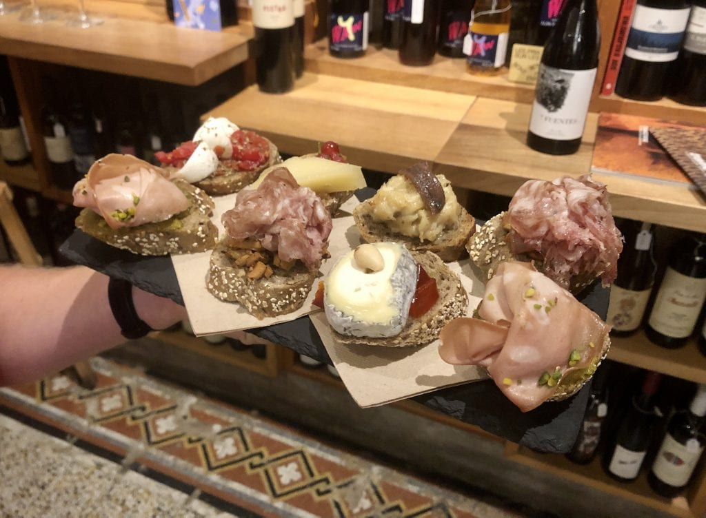 A tray with eight kinds of cicchetti on it: eight pieces of bread, each topped with a combination of cured meats and/or cheeses with nuts and/or vegetables. I loved the mortadella with pistachios and the goat cheese with roasted red peppers.