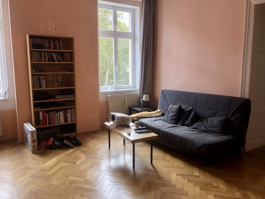 The old living room: tall wooden bookcase, wooden table with black plastic legs, and old gray futon.