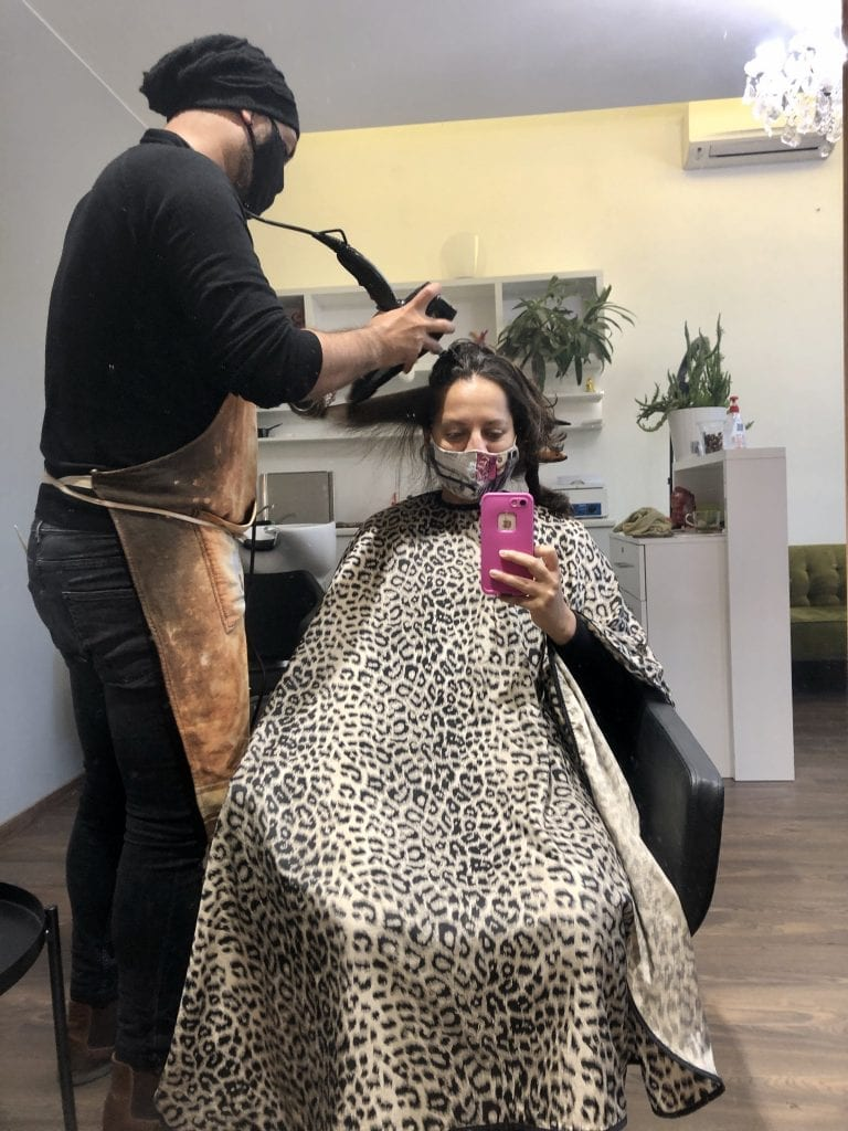 Mirror selfie of Kate getting a haircut in a leopard-print bib, wearing a mask. Her stylish wears a mask while blow-drying her hair.
