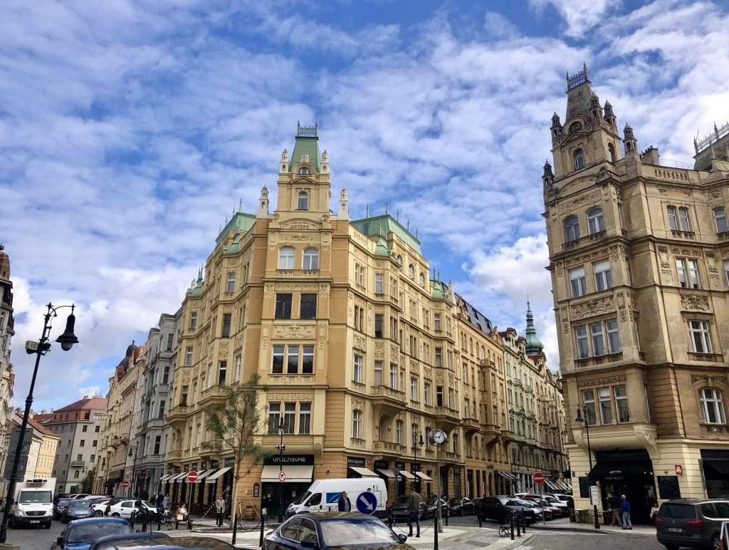 A yellow building with crenellation underneath a blue and white sky in Prague.