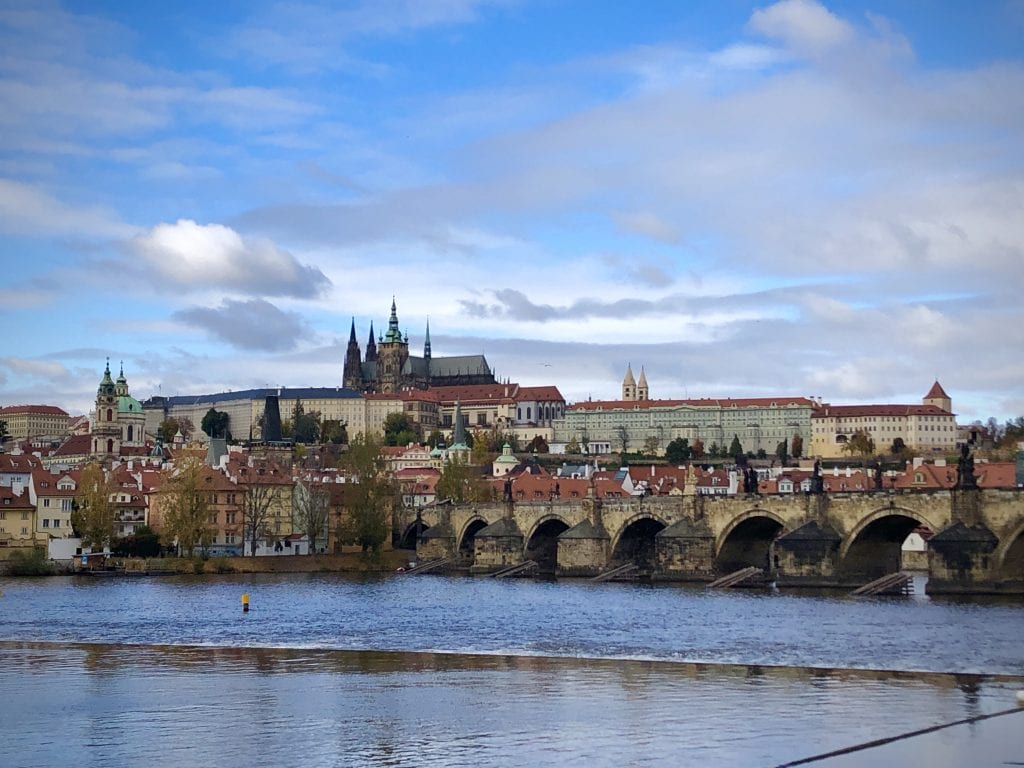 Prague Castle and St. Vitus's cathedral atop a hill; in the foreground, churches and the Charles Bridge, all set on the river.