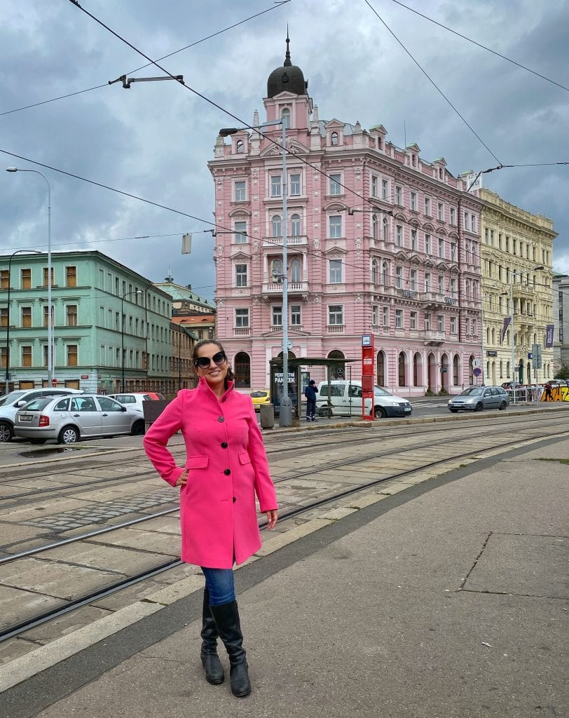Kate smiling in a hot pink peacoat that hits just above her knees with an upward facing collar. She also wears jeans and tall black boots and big black sunglasses. She is smiling and in the background is a two-tone pink crenellated building.
