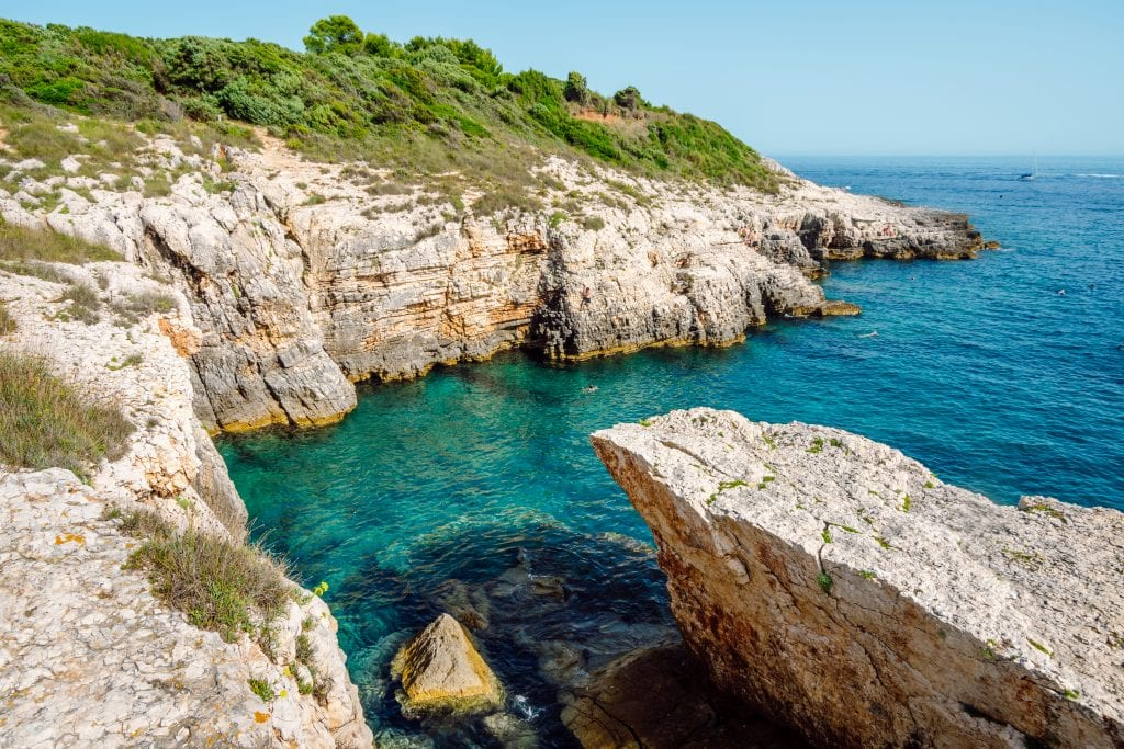 The rock slab beaches of Kamenjak, and cliffs leading down into bright turquoise water.