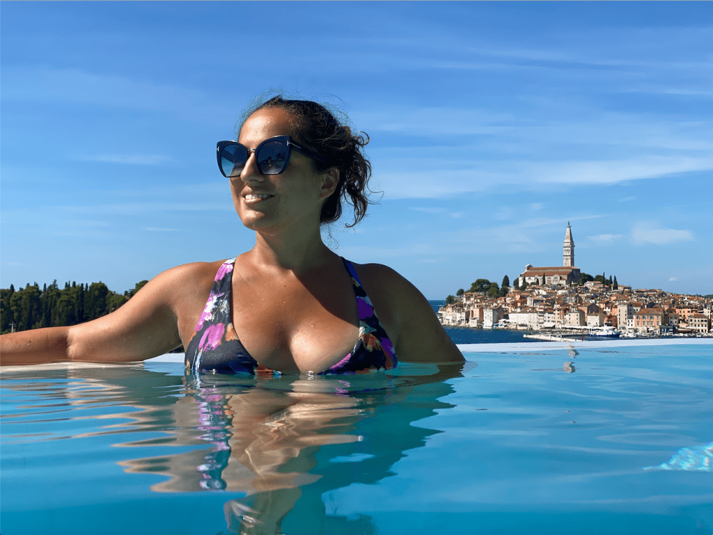 Kate smiling in sunglasses and a flowered bikini on the edge of the infinity pool, the Rovinj city skyline behind her.