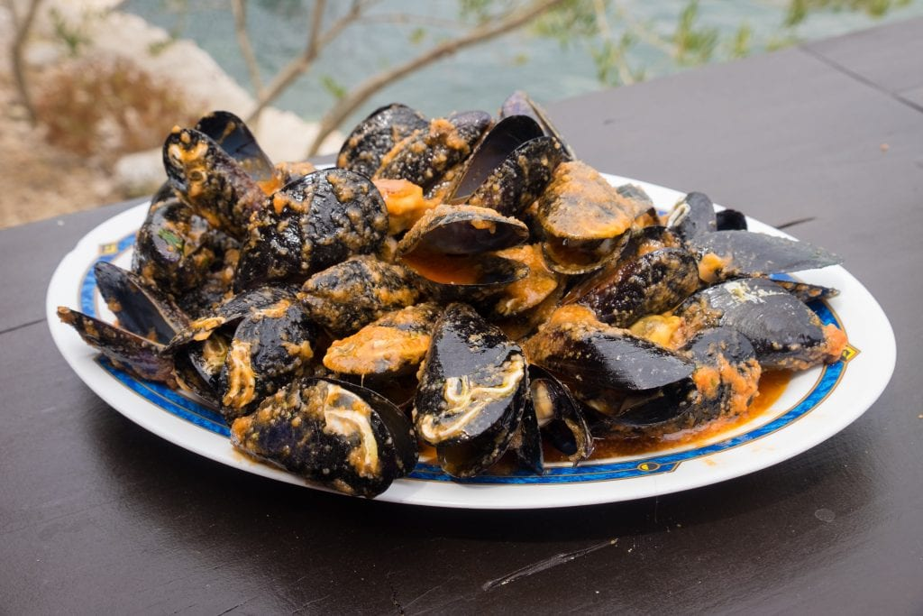 A big plate of mussels in a tomato-based sauce.